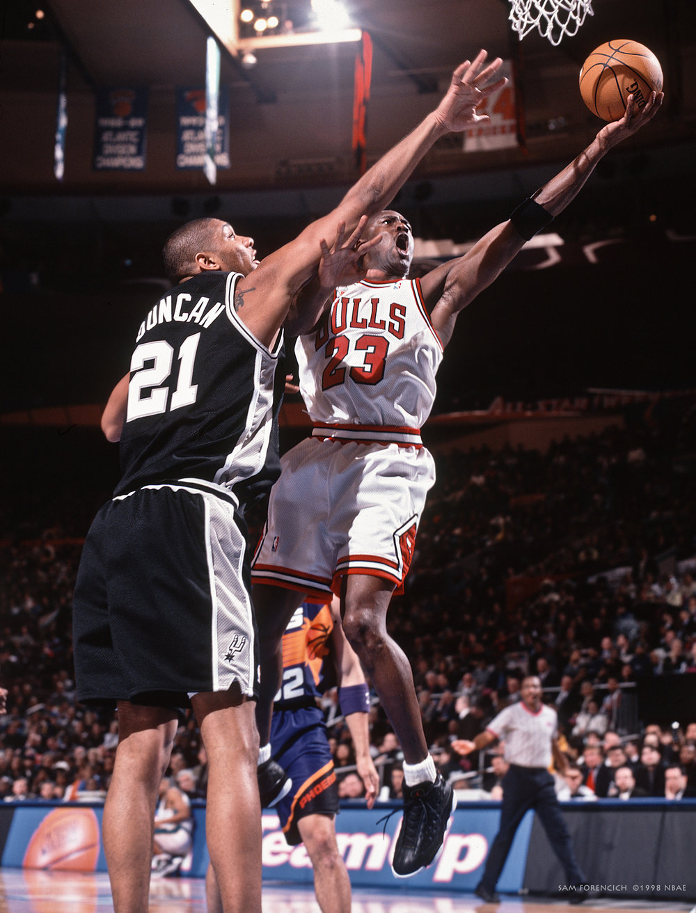 New York City, NY - Michael Jordan #23 of the Eastern Conference All-Stars goes up against Tim Duncan #21 of the Western Conference All-Stars during the 1998 NBA All-Star Game on February 8, 1998 at Madison Square Garden. Manually focused Hasselblad, RDP 100 film, arena strobe lighting.  Sam Forencich ©1998 NBAE