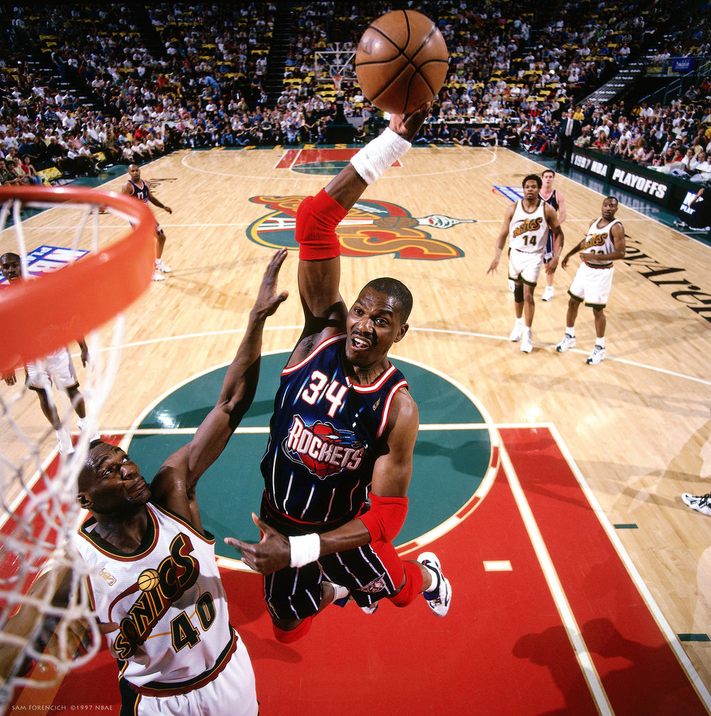 Seattle, WA - Hakeem Olajuwon #34 of the Houston Rockets goes up for a slam dunk against the Seattle Supersonics during game 4 of the Western Conference Semifinal series of the 1997 NBA Playoffs in 1997 at the Key Arena. Hasselblad remote camera, RDP 100 film, arena strobe lighting. Sam Forencich ©1997 NBAE