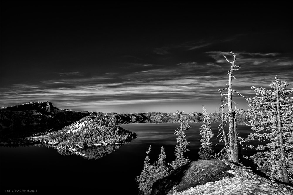 Wizard Island reflects on the surface of Crater Lake, Crater Lake National Park, Oregon. The deepest lake in the United States at 1,949 feet, Crater Lake's caldera is fed entirely from rain and snow melt. Still image from Invisible Oregon time-lapse sequence. IR converted Nikon D750, post processed gray scale conversion.  © 2016 Sam Forencich