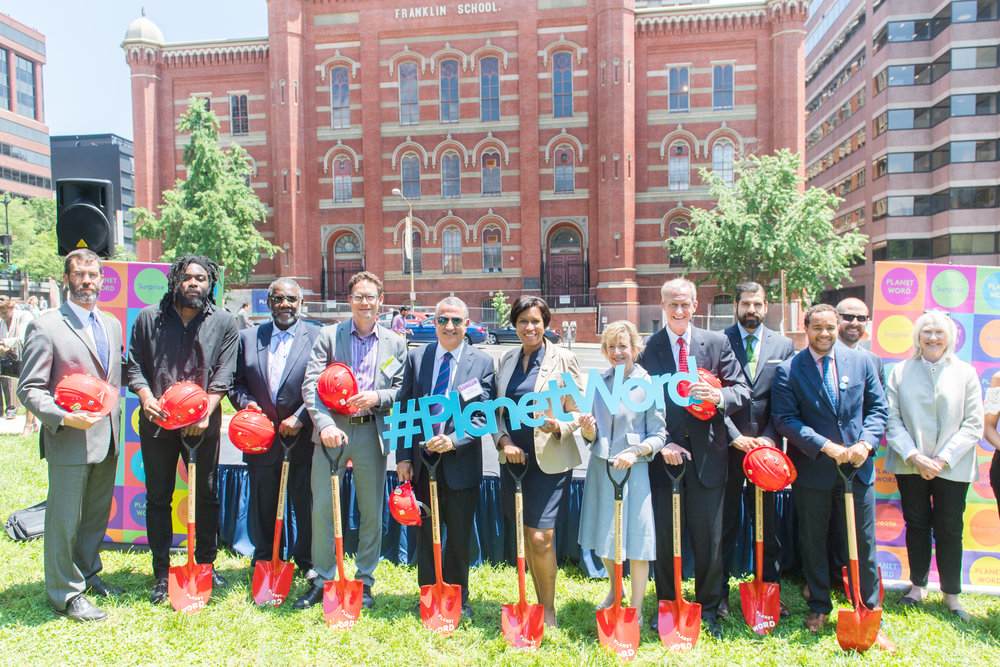 Assorted Planet Word representatives pose with hard hats and shovels in front of the Franklin School