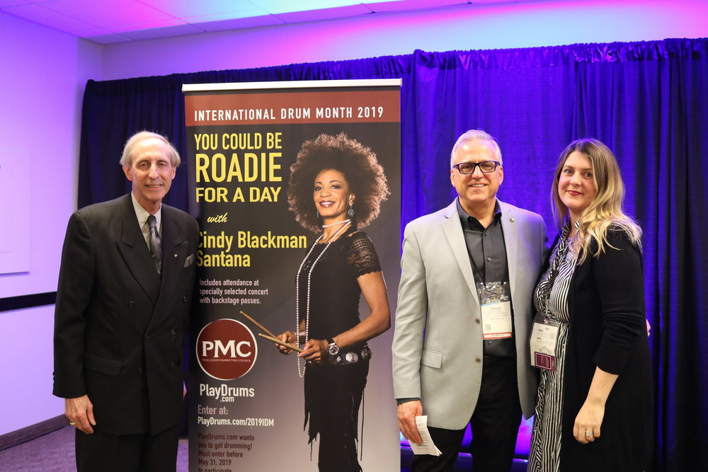 "2019  ""Roadie for a Day"" POP display featuring grand prize celebrity drummer/host Cindy Blackman Santana. (Left to Right) PMC co-executive directors: Karl Dustman (Dustman & Associates), David Jewell (Yamaha Corporation), and Jennifer Paisley (Alfred). [Photo by Victoria Wasylak, courtesy of MMR Magazine.]"