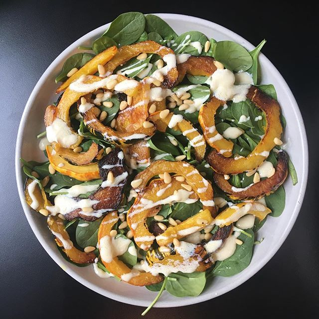 Roasted squash on top a 'bed' of spinach topped with pine nuts and a yogurt dressing ♥️ #rareandwell