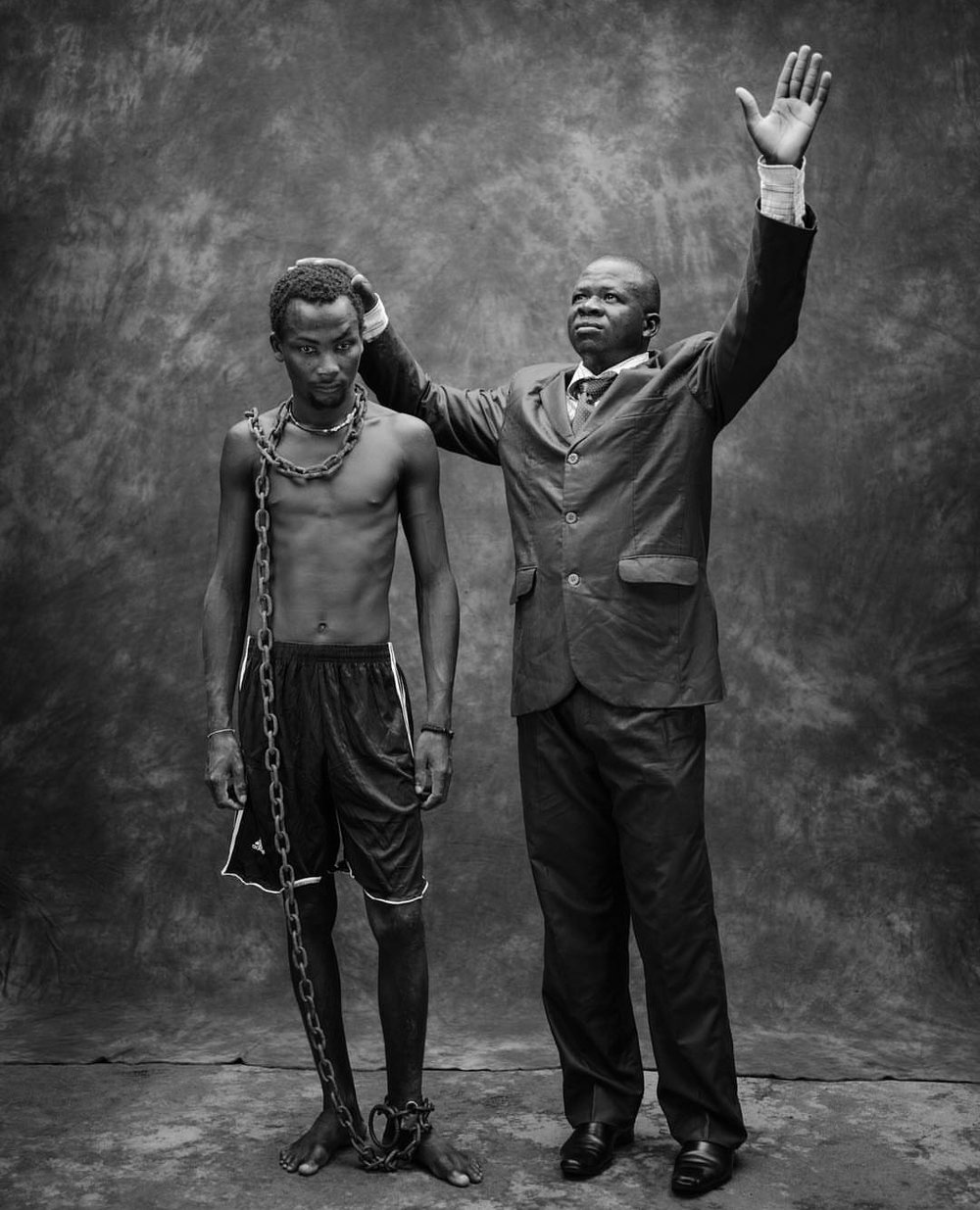 Togo: Pentacostal pastor Lare Damitote Bertrand with a chained, mentally ill man he claims to heal with prayer. Image: by Robin Hammond for National Geographic