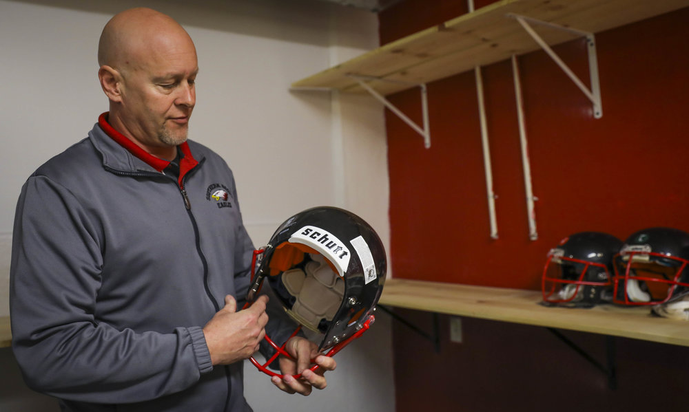 Pat Lacy, Southern Boone County R-I School District's athletic director, holds a football helmet while talking about concussion prevention at Southern Boone Middle School on Tuesday, March 21, 2017, in Ashland, Missouri. Lacy said keeping track of the number of concussions makes him more aware of youth athletes' brain injury prevention.