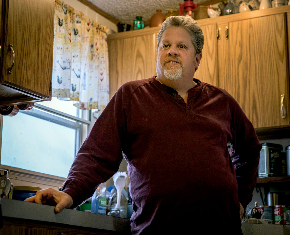 Paul Harter, farmer, talks to his wife in their home on Wednesday, Feb. 8, 2017, in Mexico, Missouri. Harter was elected to sit on a board at the Missouri Rural Crisis Center. Harter has been a farmer for 10 years, and he receives a tax credit from the Affordable Care Act to afford health insurance. Photo by Meiying Wu.