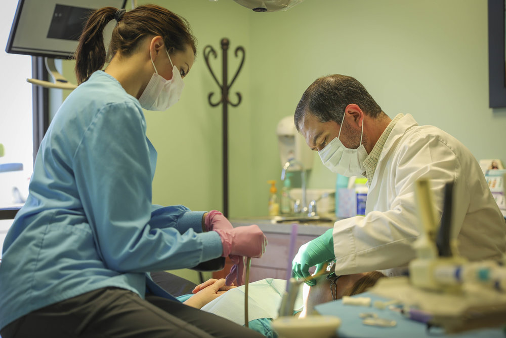 "Johnathan Mallott, the owner of Keen Dental Care, checks a patient's teeth in Columbia, Missouri on Wednesday, April 12, 2017. ""Fluoride is definitely one of those things that there's an acceptable level, and if you get too much of it, it can be a bad thing like a lot of things,"" Mallott said. Photo by Meiying Wu."