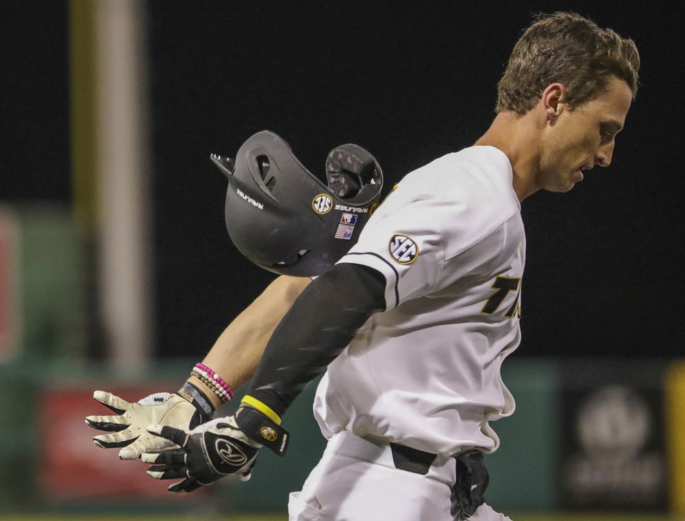 Arms stretched back, Missouri's Matt Berler reaches to catch his batting helmet that flies off his head as he sprints toward first base during a game between Missouri and Alabama A&M on Tuesday, Feb. 27, 2018 at Taylor Stadium in Columbia, Mo. The Missouri Tigers Baseball Team defeats Alabama A&M 7-3 in Missouri's first home game of the season Tuesday night.