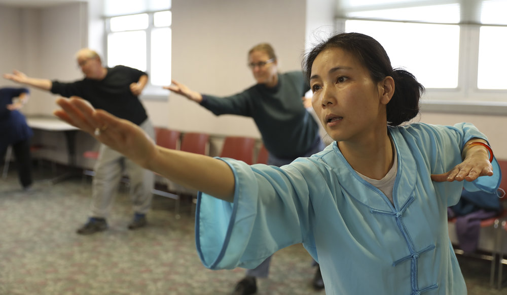 Wenfang Yang, an MU visiting scholar from Shanghai Normal University, stretches out her right arm in the Health Qi Gong class on Tuesday, March 7, 2018 at Mizzou North. MU Confucius Institute began offering this class in early January this year.