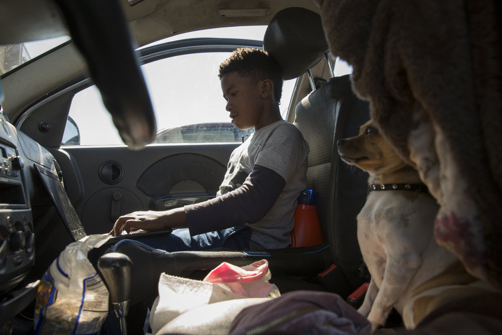David Johnson plays video games in a sedan with his dog Tinker Bell sitting next to him in Richmond, Calif., on Saturday, Oct. 13, 2018. Johnson used to live in this car with his mother, sister and Tinker Bell.