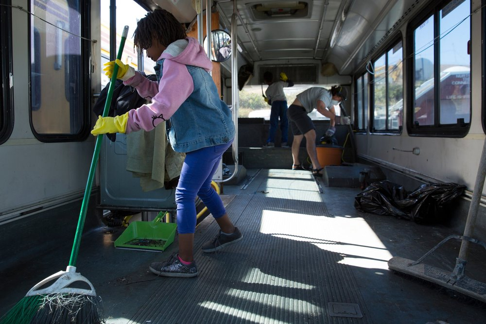 Miracle Johnson, 8, helps clean up as part of the initial phase of remodeling the bus her mother bought on a whim a few years ago.