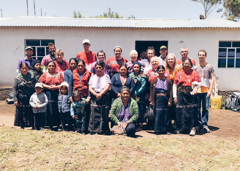 The Concord United Methodist Church Team, dressed in traditional Mayan huipiles and cortes, alongside the women who received new stoves