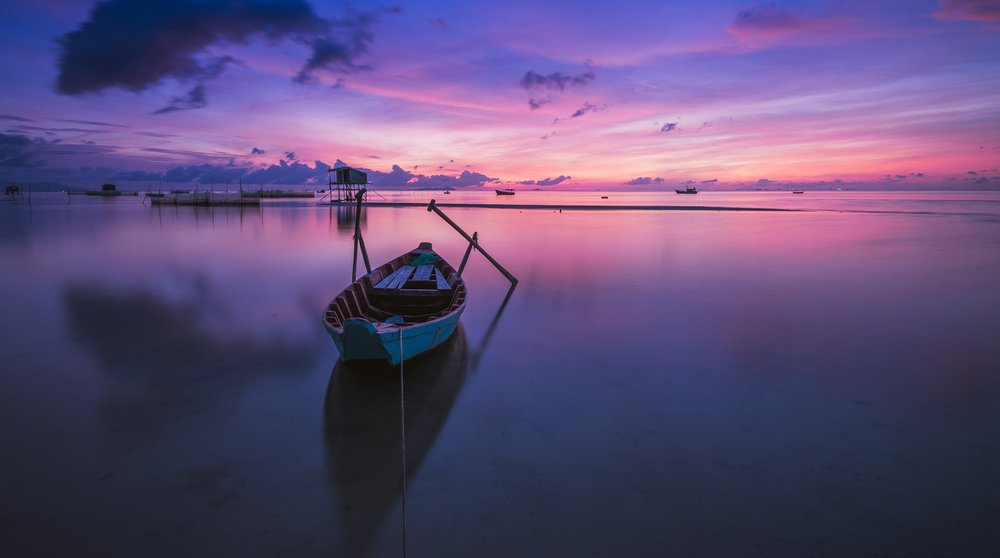 abandoned wooden boat on purple lake at sunset