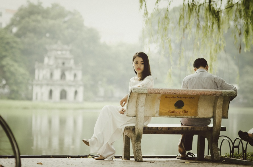 asian couple look away from one another by lake