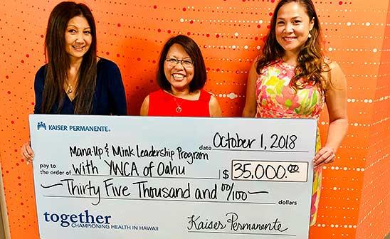 Maria Borje-Bonkowski, Regional Compliance Officer, Kaiser Permanente Hawaii (center) presenting grant to Mana Up's Meli James (left) and Terri Funakoshi.