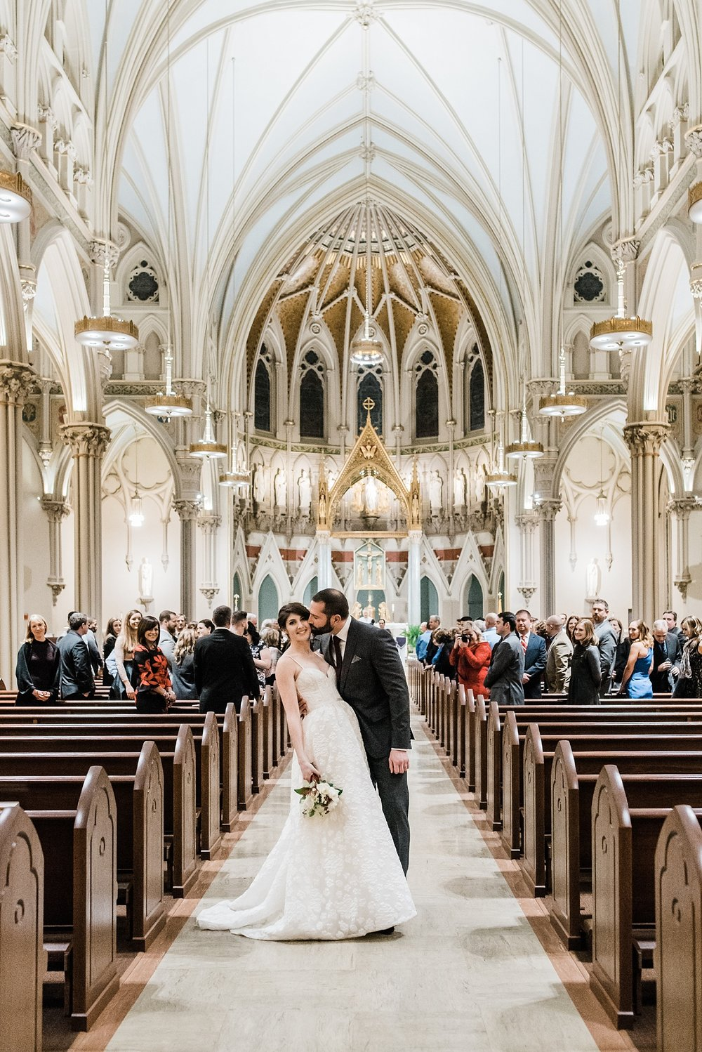 couple kissing in aisle in immaculate conception church lowell