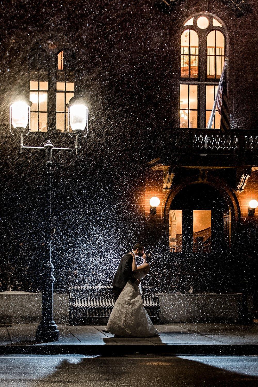 groom dips bride in snowy night photo