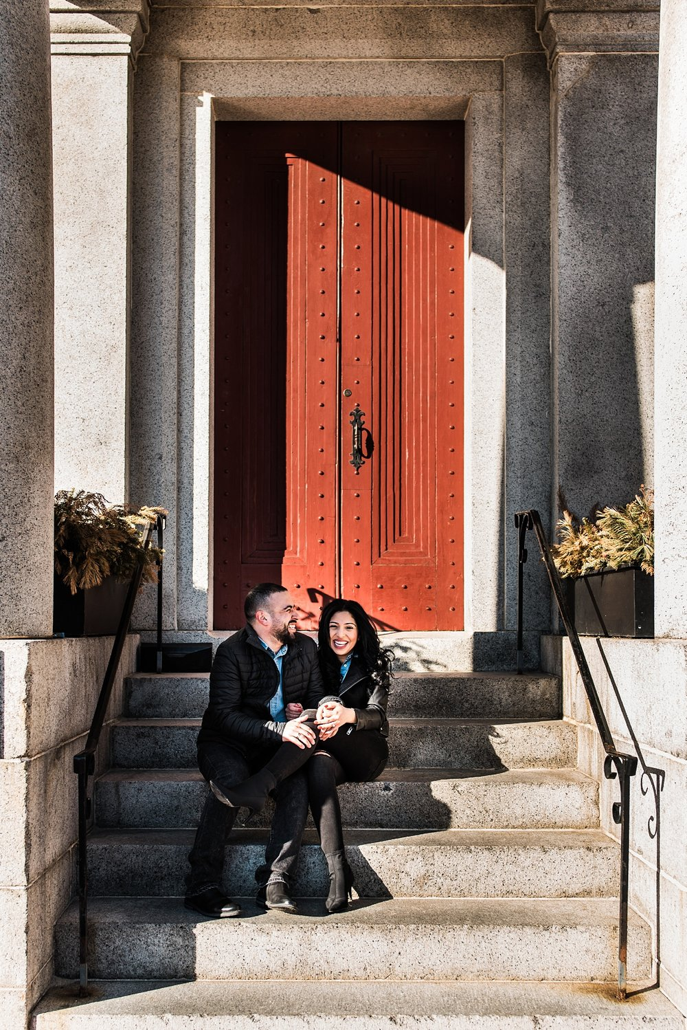 engagement photo of couple on steps laughing