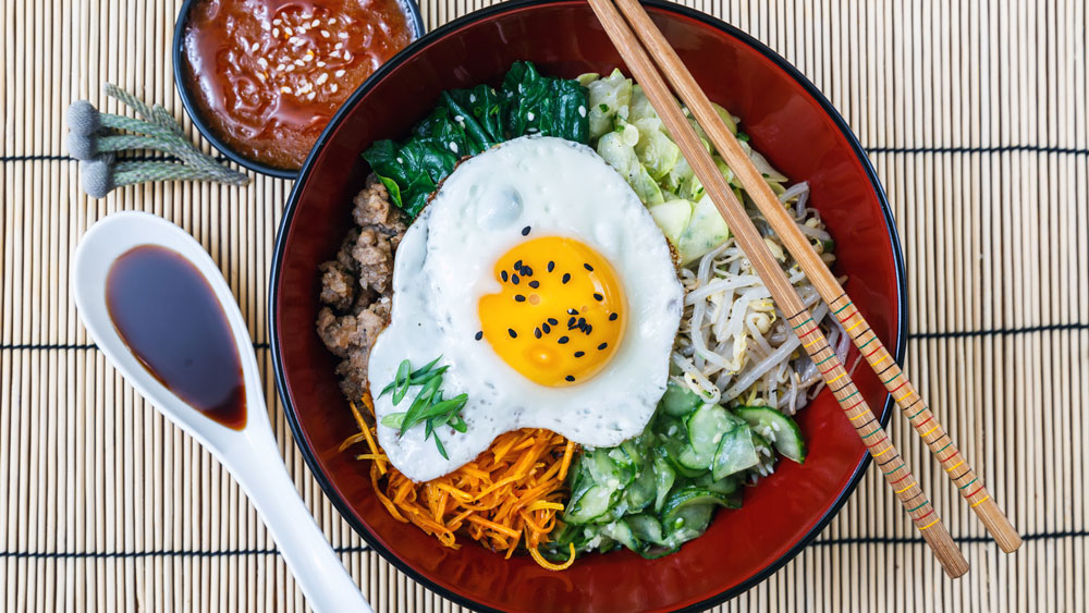 "Bibimbap means ""mixed rice"". Bibimbap is served as a bowl of warm white rice topped with namul and gochujang, soy sauce, or doenjang."
