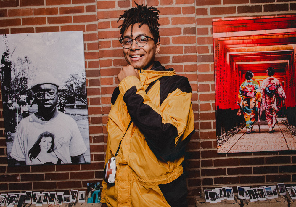 Photo of Chollette next to his own artwork. Captured by Jasmine King