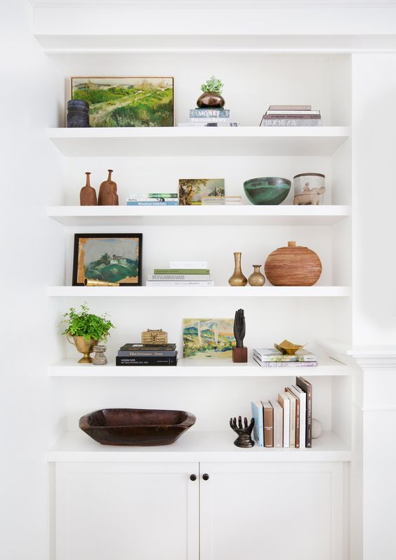 Have a bookcase or floating shelves? Style them up with all of your favorite books, photos, mementos, and be sure to add some greenery!