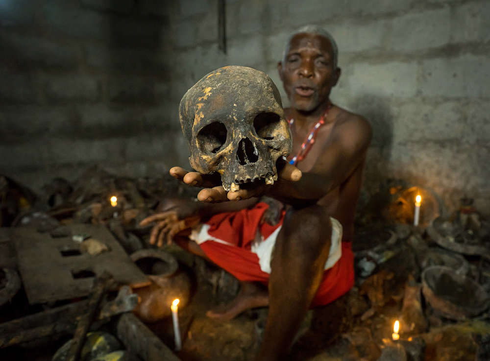 Benin, West Africa. The  bopa dah tofa  voodoo master showing skulls of criminals killed by Heviosso, the god of thunder, that he collects.
