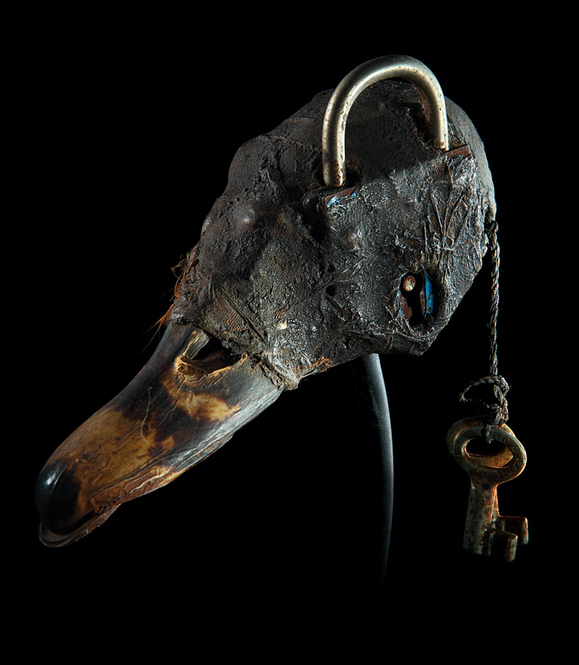 A Fon  vodun  (voodoo) object from Benin. Duck skull and bill, lock, keys, cloth, feather, clay, sacrificial patina.