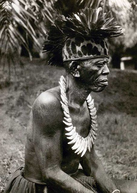 """Chief from the Lokele tribe, western Congo. Feather headdresses and leopard-tooth necklaces were typically seen on chiefs in the African """"interior"""".(1937)"""