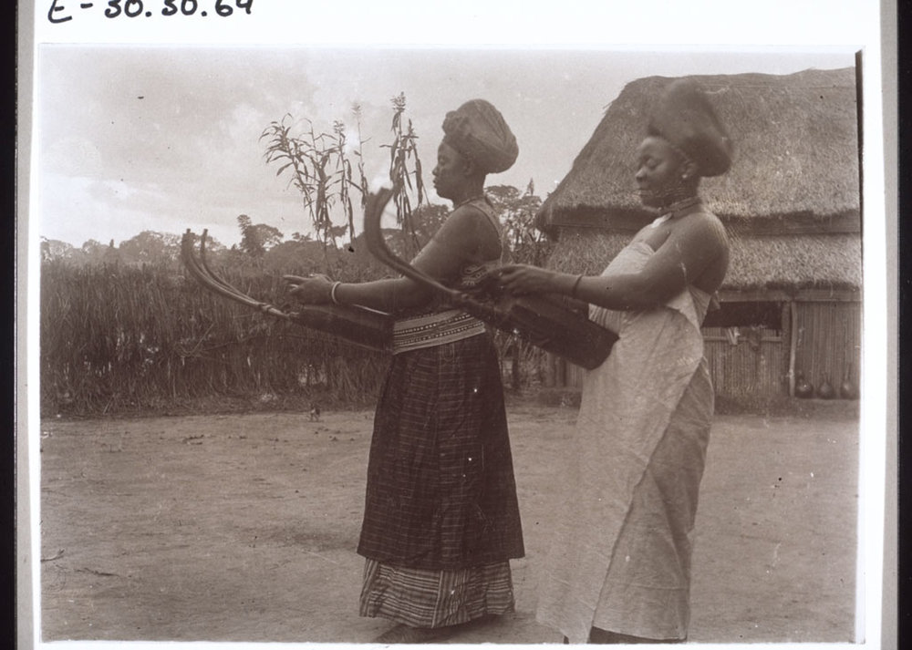 Tuke and Mowue, two of the King's wives, playing the guitar. Cameroon, 1913.