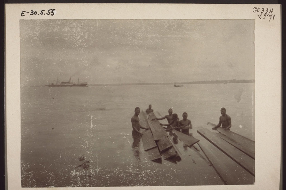 Landing boards for a Christian mission's carpentry shop in Bonaku, Douala, Cameroon, 1900. In the background, a steamer and a launch.