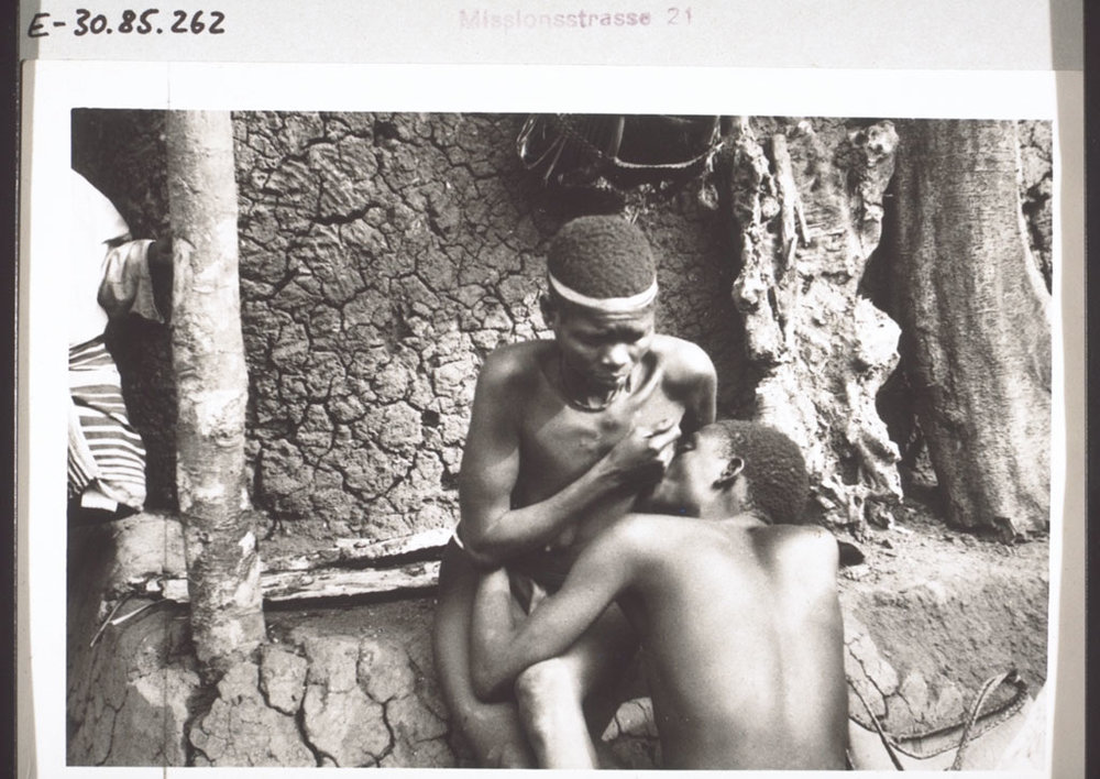 A doctor sucks blood from a sick woman. Cameroon, early 1930s.
