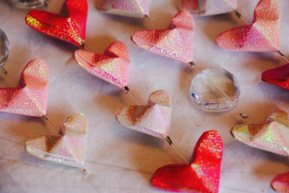 A close-up of my little origami hearts and crystal beads crimped in place on the lines.