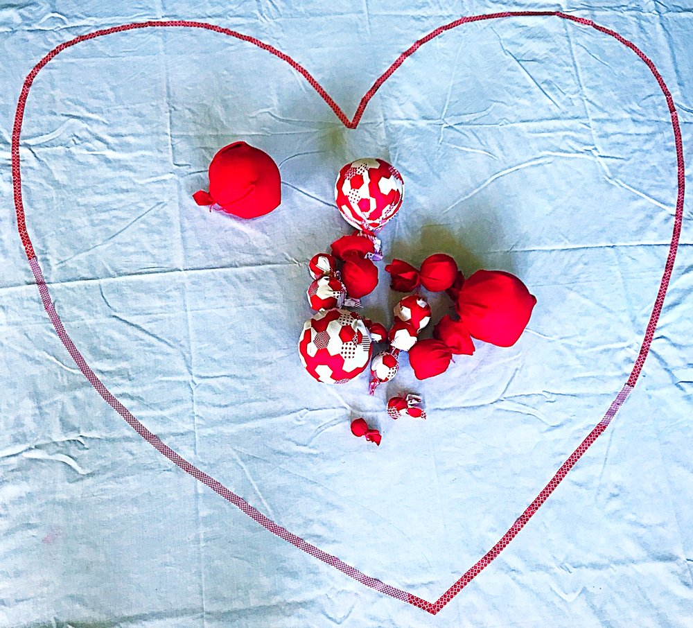 I often start with a white sheet on the floor as it gives me good contrast and clear perception of shapes and spaces. I wrapped paper and polystyrene balls in beautiful cotton linen. I varied the amount of fabric so the shapes represented both budding red roses and those in full bloom!