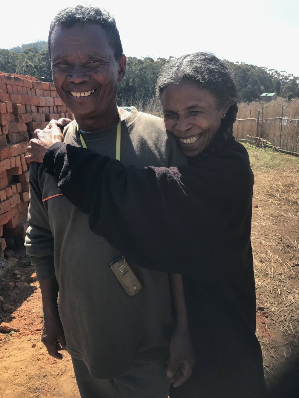 Neny Doline and Dada Michel embracing each other in their farm.