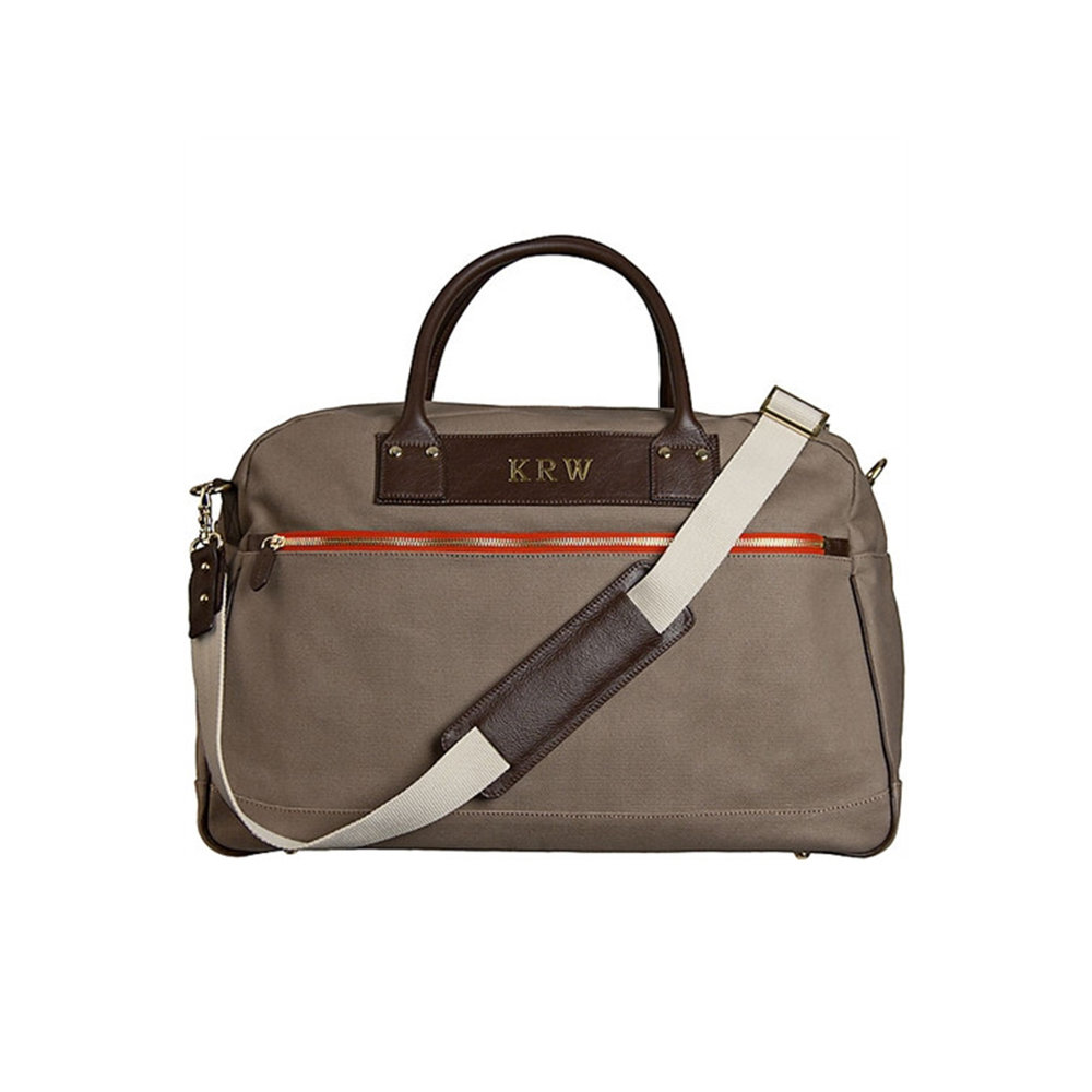 CHARLIE DUFFLE - LADYBIRDRugged canvas and coffee colored leather trim, the Charlie Duffle is the perfect gift for the person in need of a duffle upgrade. Gold-toned hardware and personalized monogram provides a sense of luxury style to any weekend get away.image: ladybirdfashion.com