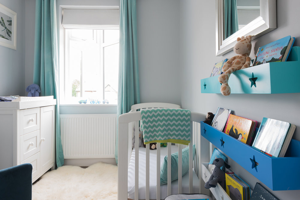 View of changing table, bookshelf and cot in peacock coloured unisex nursery