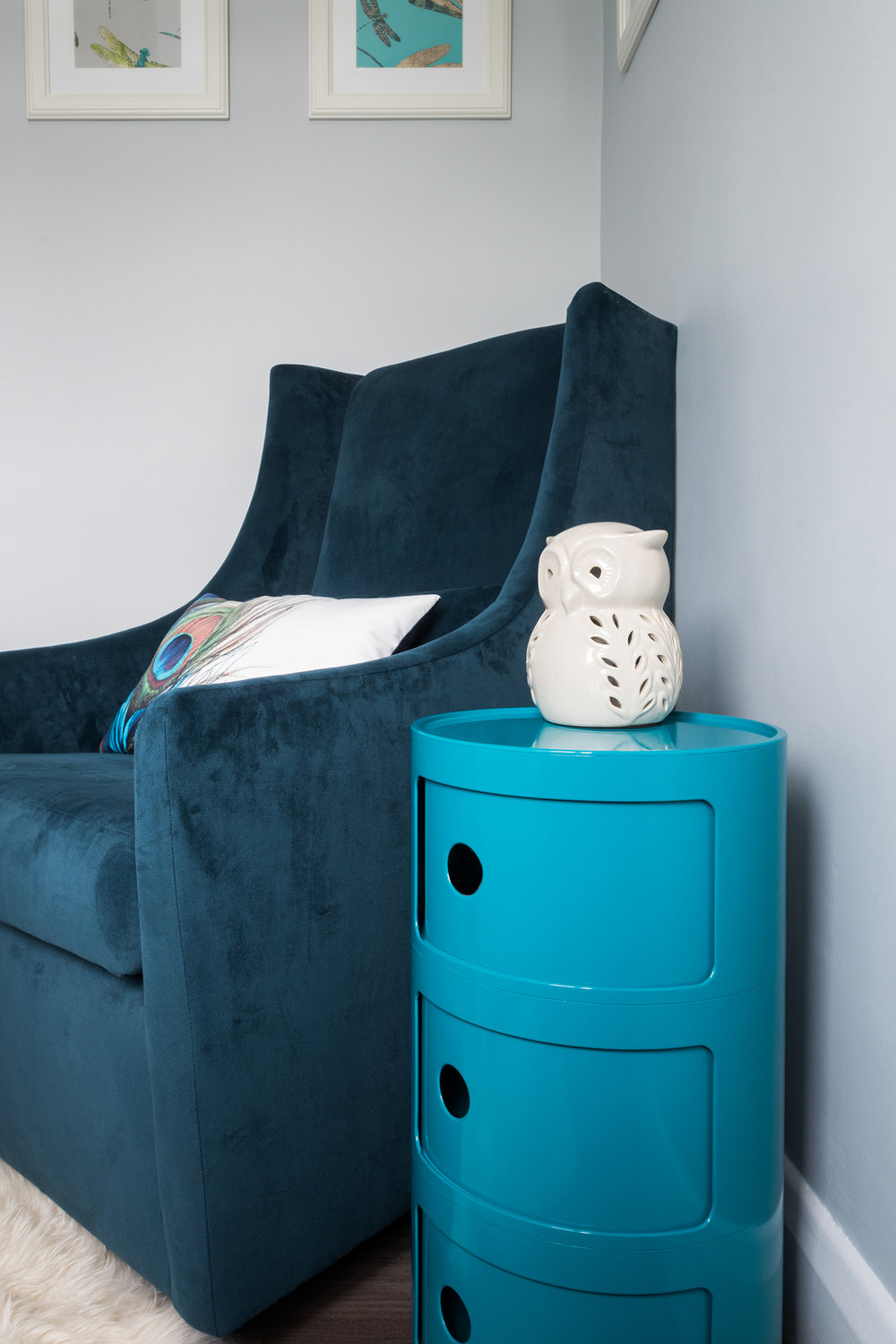View of rocking chair and sidetable in peacock coloured unisex nursery