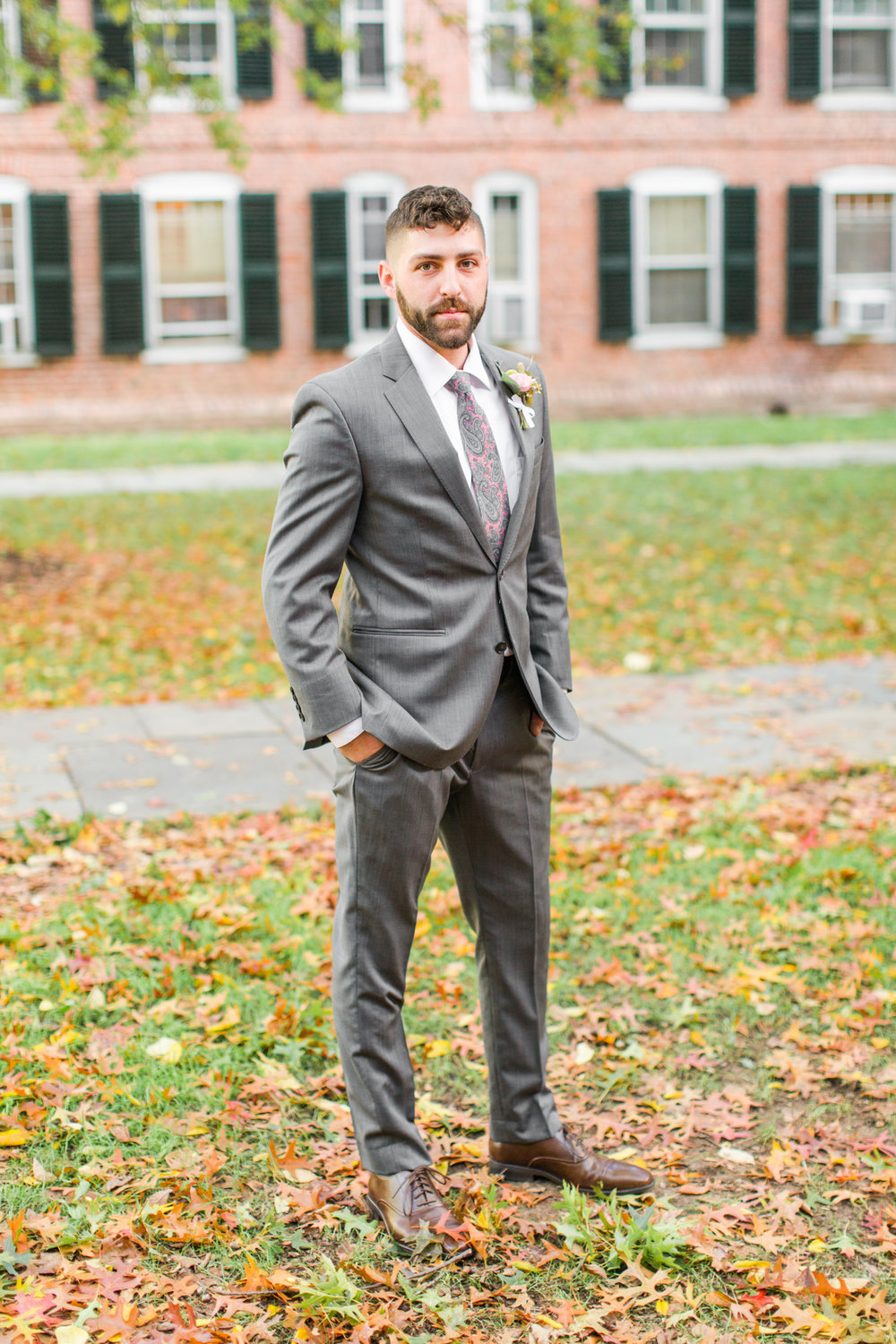Daper groom all ready to meet his bride in his grey two piece suit and pink paisely tie- Pearl Weddings & Events