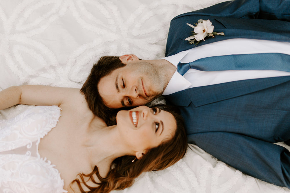 What a great couple session photo with the bride and groom lying on the ground! - Pearl Weddings & Events