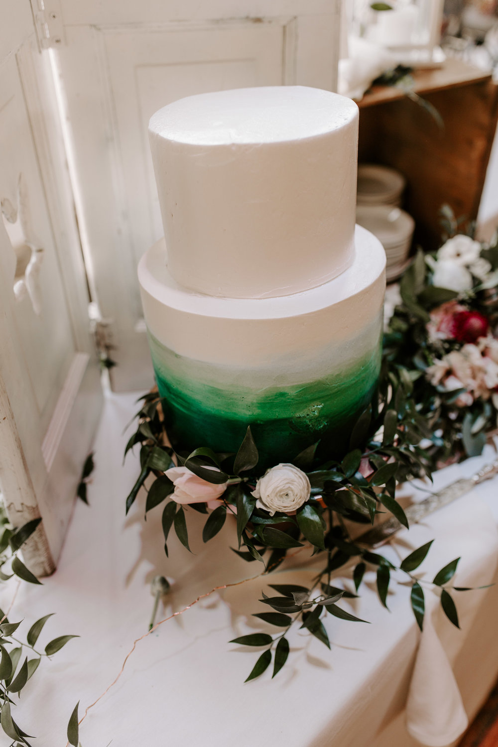 White and green tiered wedding cake with greenery! - Pearl Weddings & Events