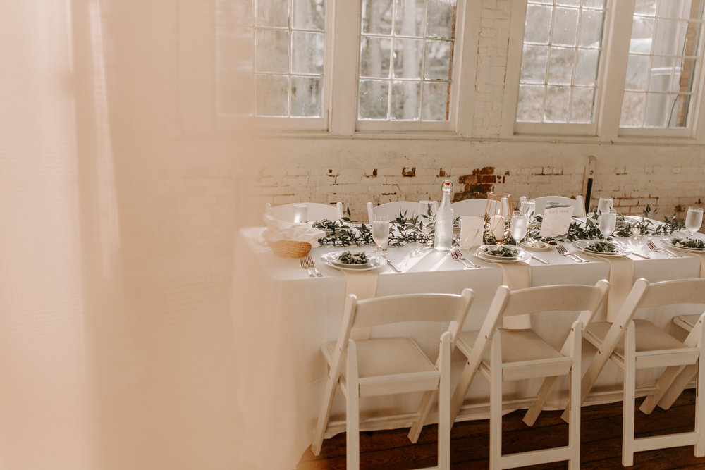 Simple white table seatings with greenery at The Lace Factory - Pearl Weddings & Events