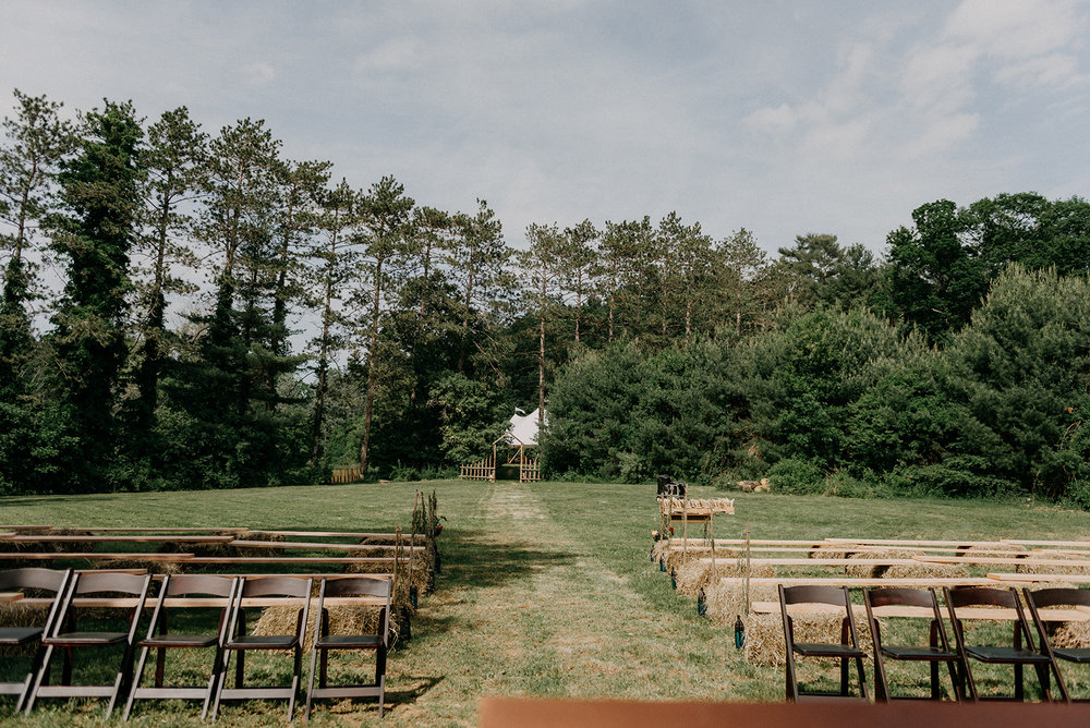 Secret garden ceremony space with benches and antique rugs - Pearl Weddings & Events