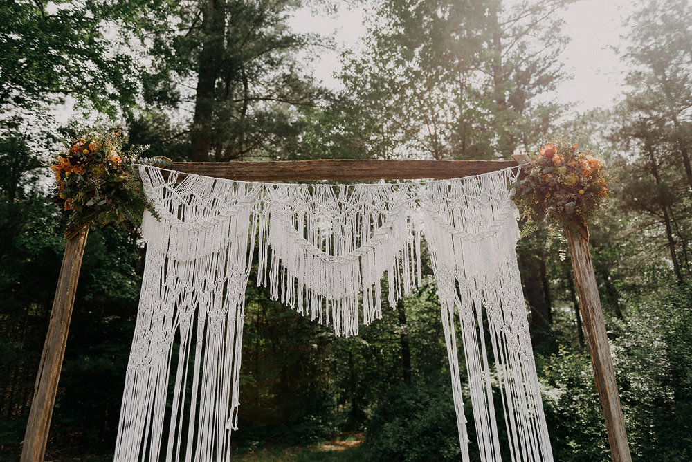Macrame back drop with wooden arch for a wedding ceremony at an outdoor wedding on an antique farm - Pearl Weddings & Events