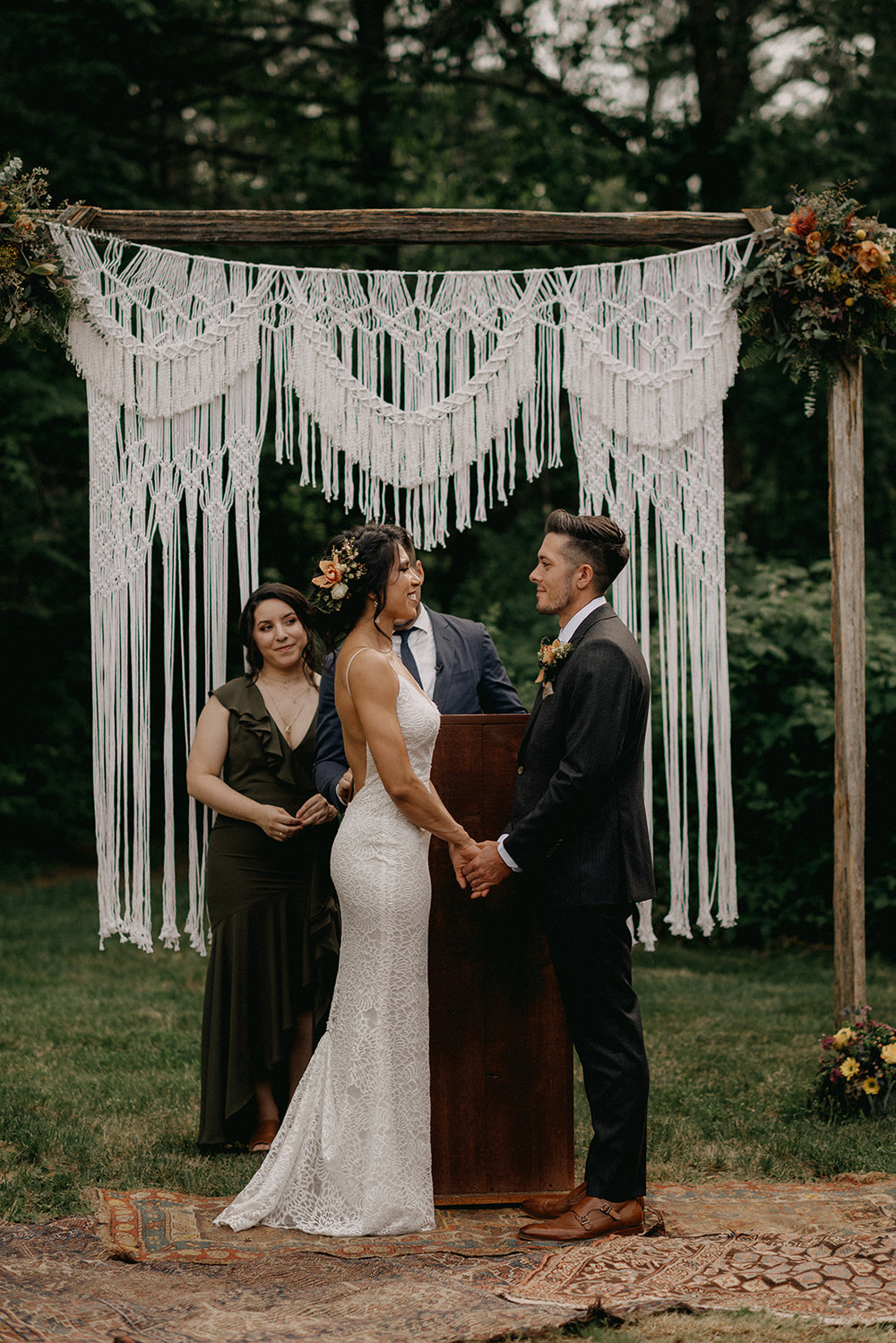 Bride and groom at their macrame wedding ceremony altar with antique rugs - Pearl Weddings & Events