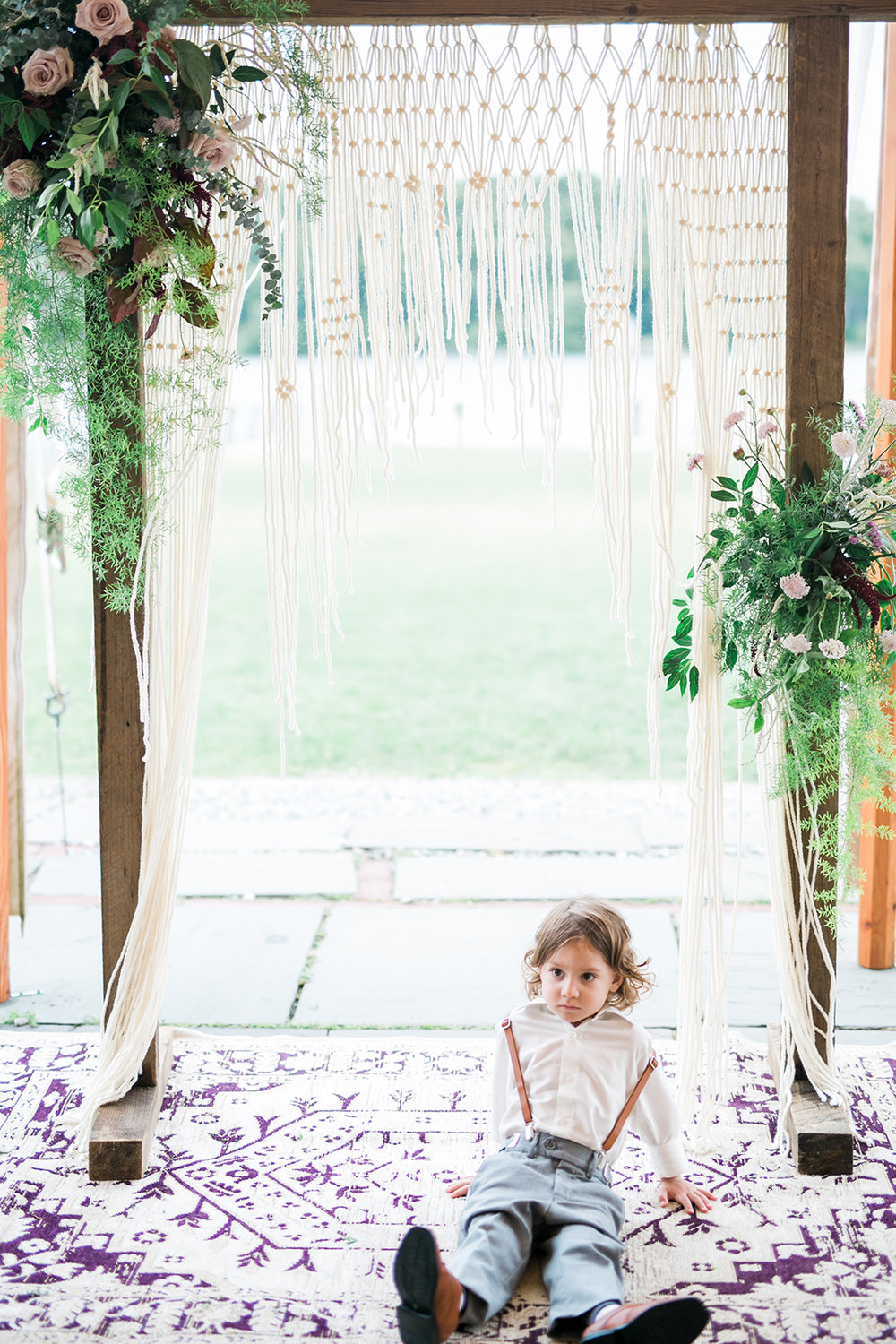 Wooden arch, asymmetrical floral, macrame, vintage rug and ring bearer all at the ceremony space - Pearl Weddings & Events