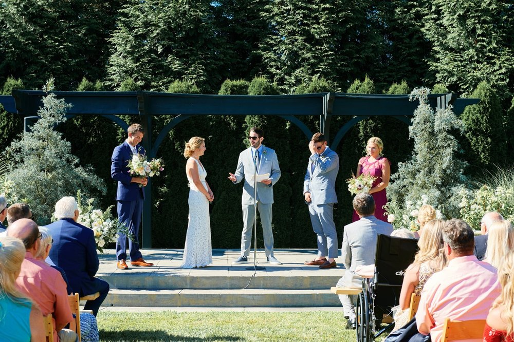 Bride and groom at the altar of The Farmers Daughter while the brides brother holds her flowers! - Pearl Weddings & Events