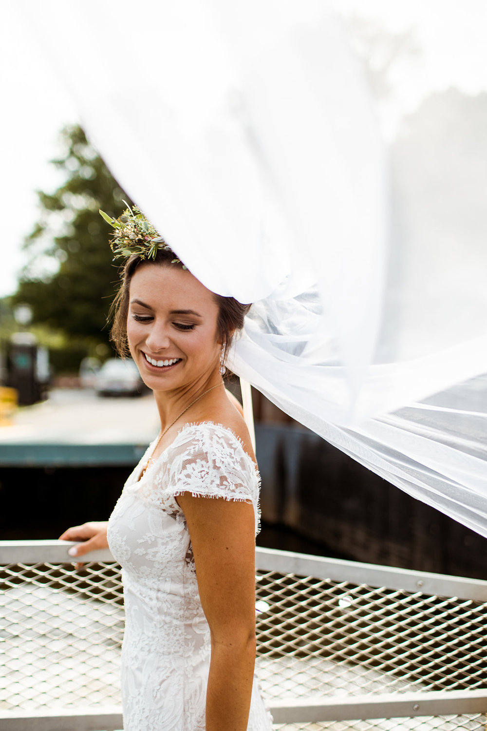 Bride with her blowing veil and beautiful floral crown by the water in Chester, CT - Pearl Weddings & Events
