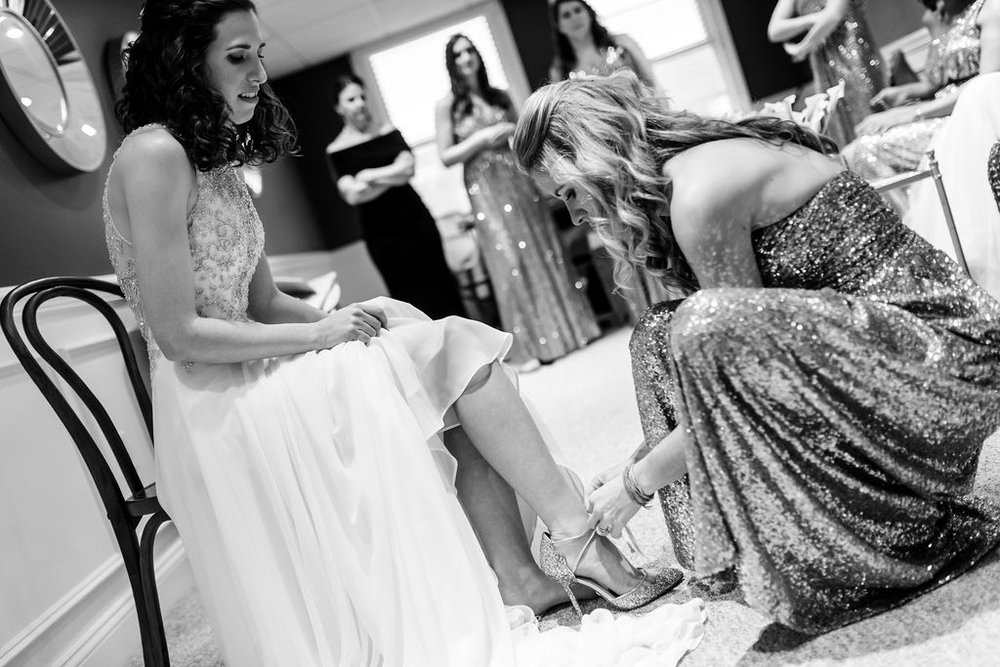 Bridesmaids helping out the bride with her shoes - Pearl Weddings & Events