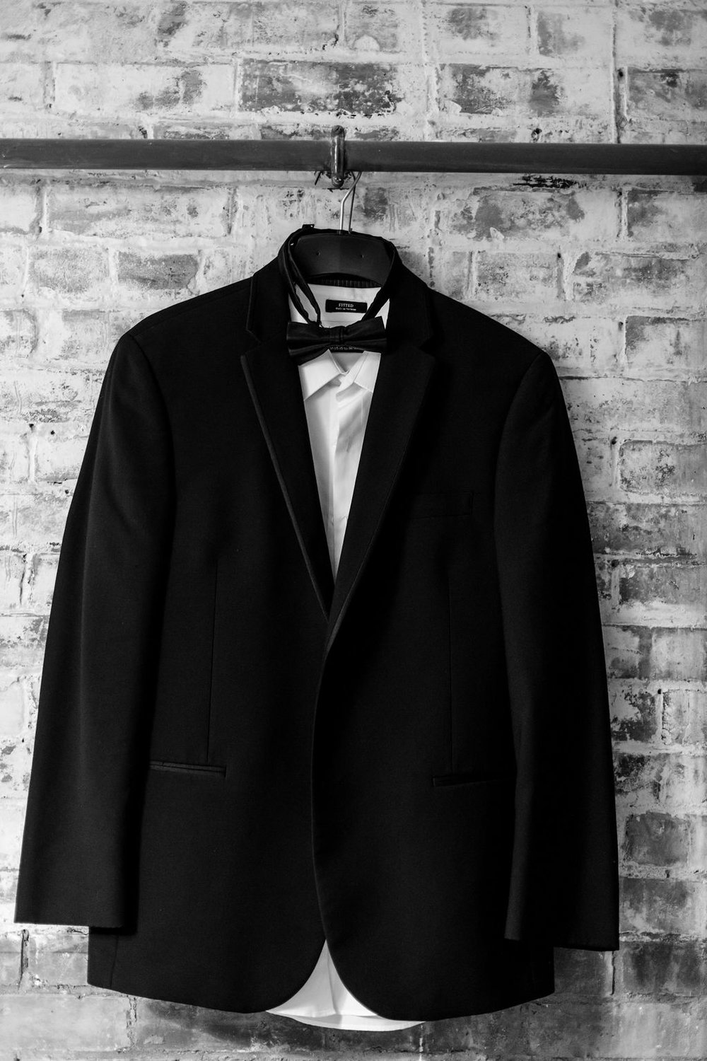 Mens black suit jacket, white undershirt with bow tie - Pearl Weddings & Events