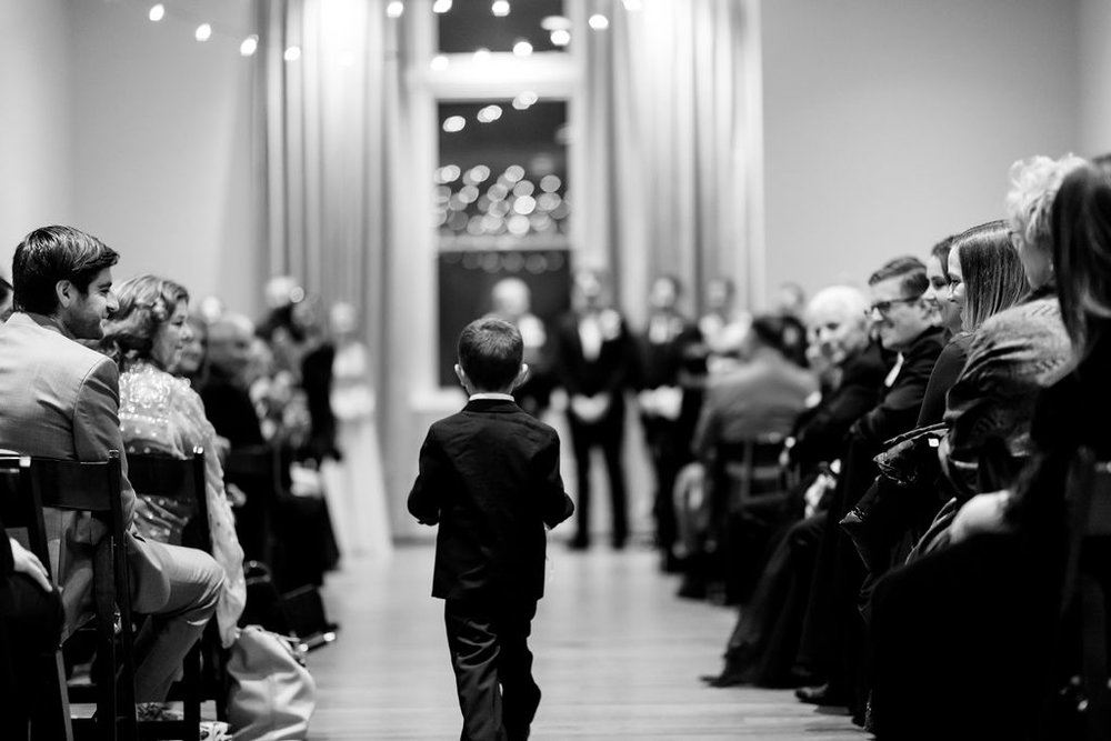 ring bearer walking down the aisle at 19Main - Pearl Weddings & Events
