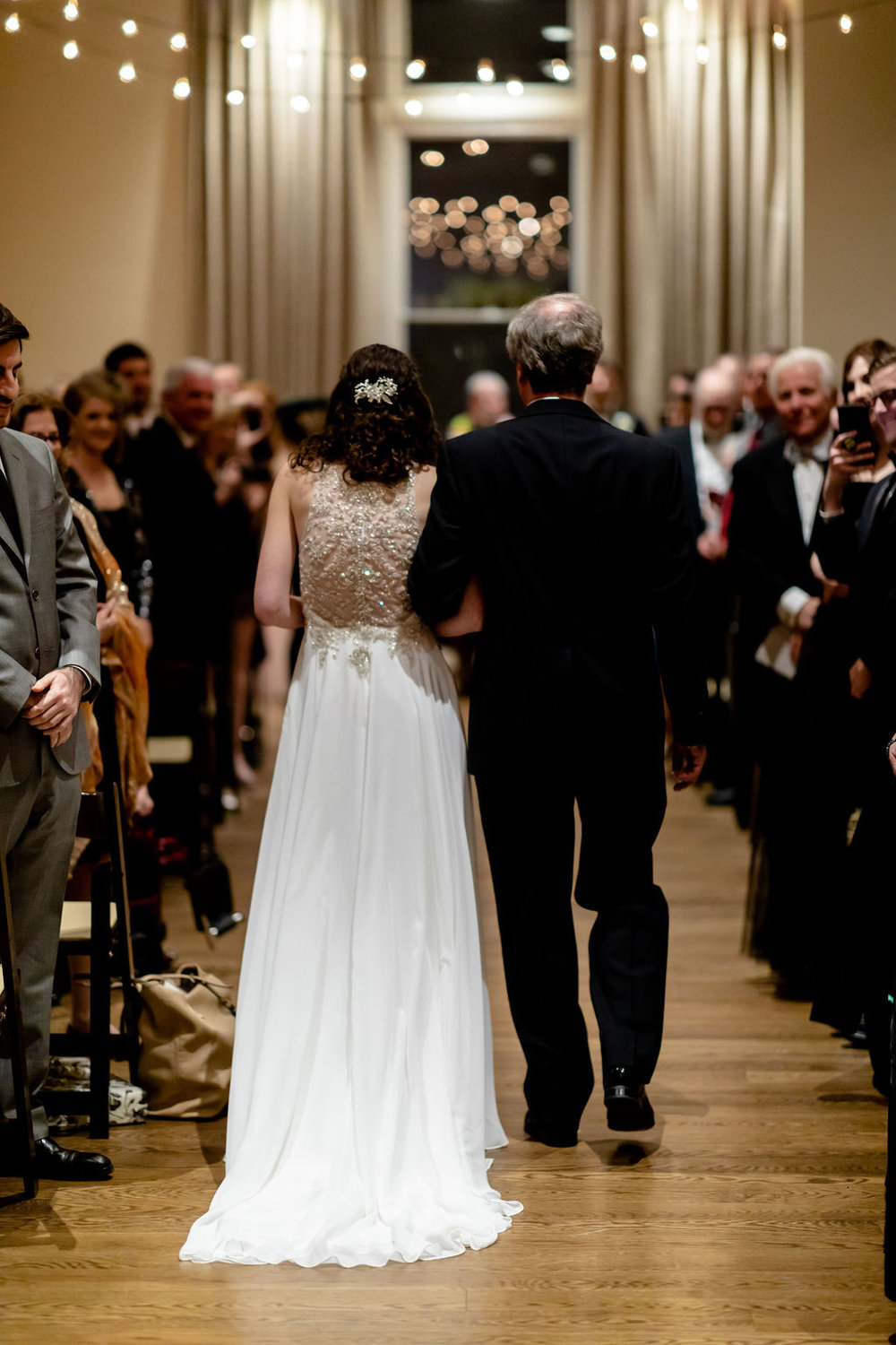 Bride and father walking down the aisle with brown folding chairs and cafe lighting above the aisle - Pearl Weddings & Events